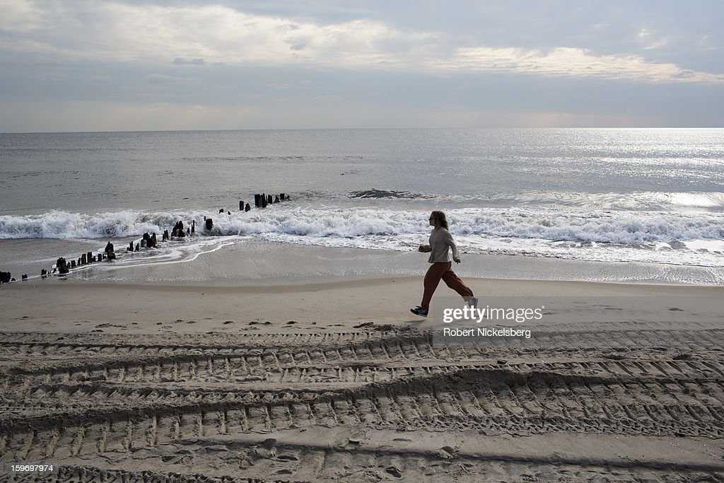 A woman jogs along the beach January 17, 2013 where a boardwalk had been removed after being damaged during Hurricane Sandy in the Rockaways January 17, 2013 in the Queens borough of New York. A $50.7 billion Superstorm Sandy aid package was voted through the House of Representatives recently. The funding would be spent on New York and New Jersey transit systems and for the Federal Emergency Management Agency's disaster relief fund.