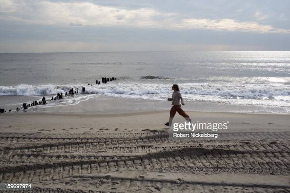 A woman jogs along the beach January 17 2013 where a boardwalk had been removed after being damaged during Hurricane Sandy in the Rockaways January...