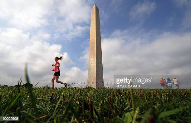 A woman jogs as tourists visit the Washington Monument in Washington DC on August 22 2009 The Washington Monument is the most prominent structure in...