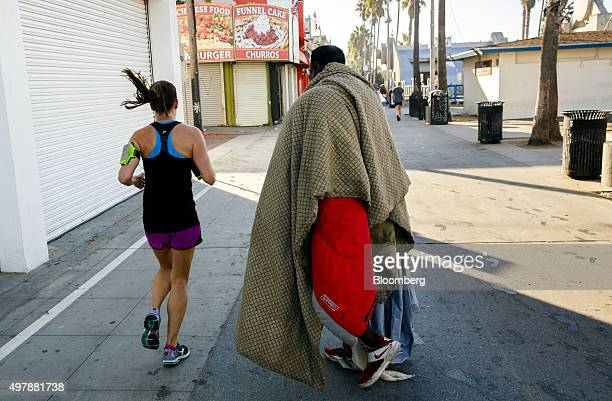A woman jogs past a man walking on the Venice Beach boardwalk in Los Angeles California US on Friday Oct 9 2015 Homelessness is on the rise in many...
