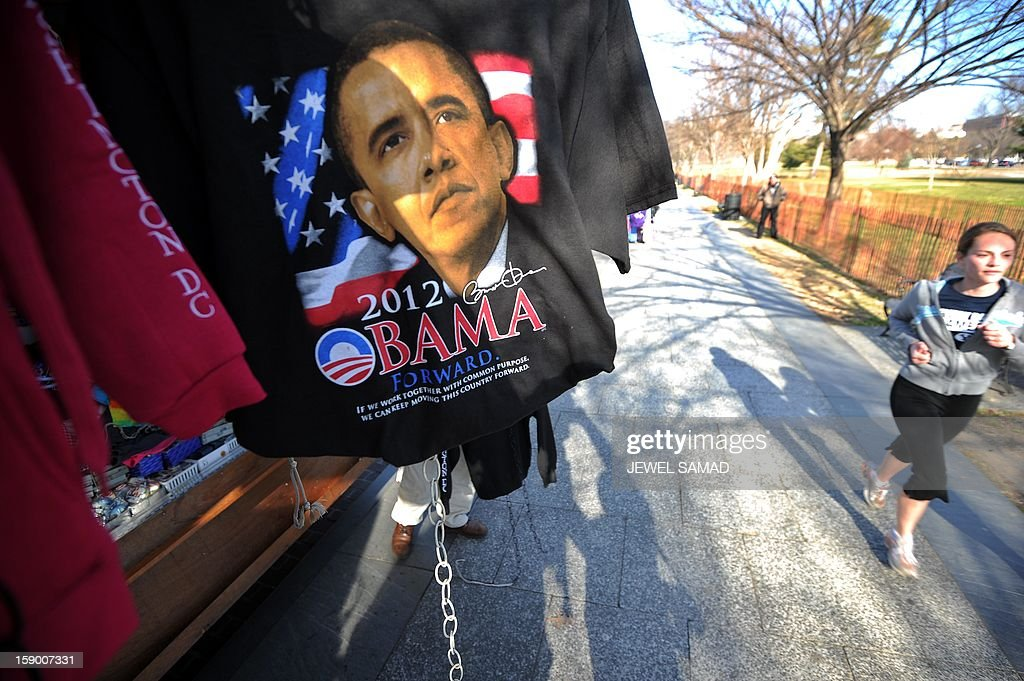 A woman jogs past a roadside souvenir stall displaying T-shirt with US President Barack Obama's picture in Washington, DC, on January 5, 2013. Preparations are underway for Obama's second inauguration which will take place with a public ceremonial oath of office on January 21, 2013. AFP PHOTO/Jewel Samad