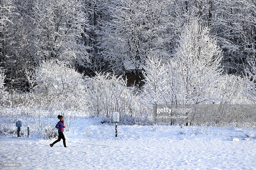 A woman jogs through a snow-covered Tom Tudek Memorial Park, in State College, Pennsylvania, Thursday, February 14, 2013.