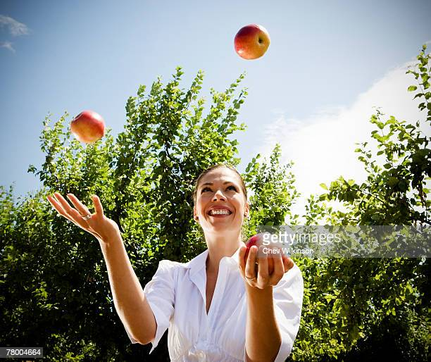 Woman juggling apples in orchard.