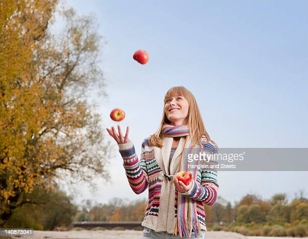 Woman juggling apples outdoors