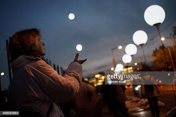 A woman juggling illuminated balls as people walk among a light installation of balloons tethered to lamps illuminating the course of the Berlin Wall...