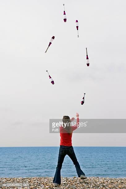 Woman juggling on beach, rear view