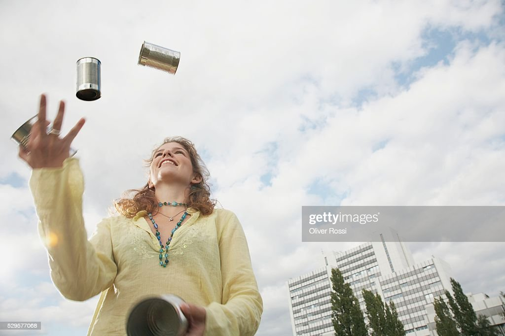 Woman Juggling Tin Cans : Stockfoto