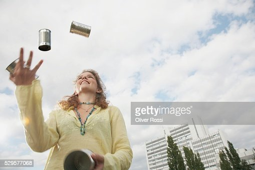 Woman Juggling Tin Cans : Stock Photo