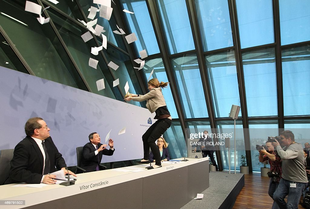 A woman jumped on the table throws papers and confetti as she interrupts a press conference by Mario Draghi, President of the European Central Bank, (ECB) following a meeting of the Governing Council ain Frankfurt / Main, Germany, on April 15, 2015. AFP PHOTO / DANIEL ROLAND / AFP / DANIEL ROLAND