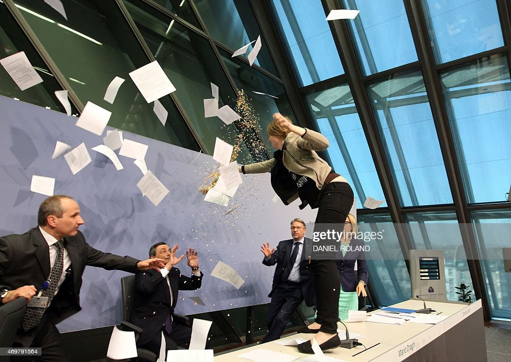 A woman jumped on the table throws papers and confetti as she interrupts a press conference by <a gi-track='captionPersonalityLinkClicked' href=/galleries/search?phrase=Mario+Draghi&family=editorial&specificpeople=571678 ng-click='$event.stopPropagation()'>Mario Draghi</a> (C), President of the European Central Bank, (ECB) following a meeting of the Governing Council in Frankfurt / Main, Germany, on April 15, 2015. AFP PHOTO / DANIEL ROLAND / AFP / DANIEL ROLAND