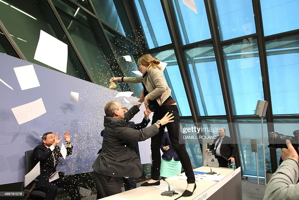 A woman jumped on the table throws papers and confetti as she interrupts a press conference by Mario Draghi (C), President of the European Central Bank, (ECB) following a meeting of the Governing Council in Frankfurt / Main, Germany, on April 15, 2015. AFP PHOTO / DANIEL ROLAND