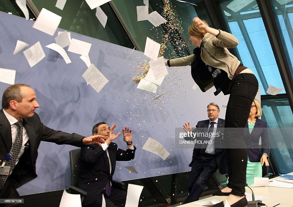 A woman jumped on the table throws papers and confetti as she disrupts a press conference by <a gi-track='captionPersonalityLinkClicked' href=/galleries/search?phrase=Mario+Draghi&family=editorial&specificpeople=571678 ng-click='$event.stopPropagation()'>Mario Draghi</a> (C), President of the European Central Bank, (ECB) following a meeting of the Governing Council ain Frankfurt / Main, Germany, on April 15, 2015. The woman who charged at Draghi calling for an 'end to the ECB dictatorship' was quickly escorted out of the premises by security officers before the news conference resumed. AFP PHOTO / DANIEL ROLAND