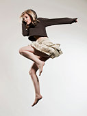 Woman jumping against gray background
