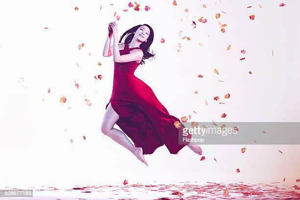 Woman jumping amongst leaves