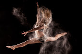 Woman jumping and dancing in a cloud of  powder