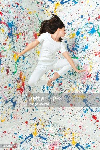 Woman ジャンプで覆った壁のペイントと : ストックフォト