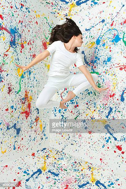 Woman jumping and walls covered in paint