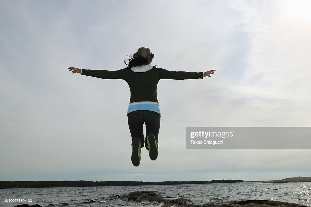 Woman jumping by sea, rear view : Stock Photo