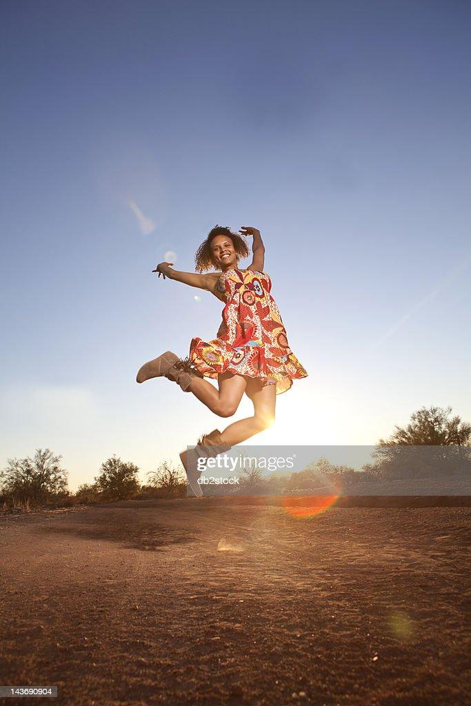 Woman jumping for joy in desert : Stock Photo