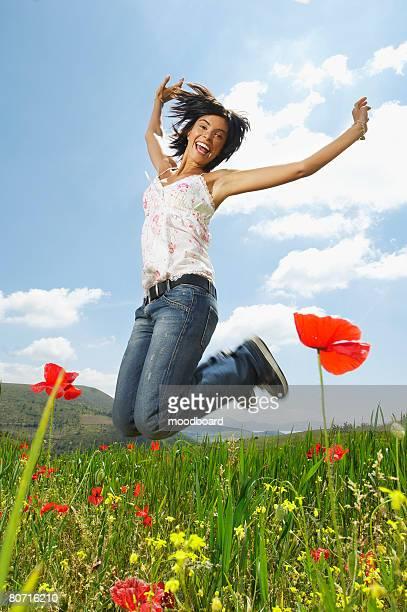 Woman jumping for joy in mountain meadow portrait