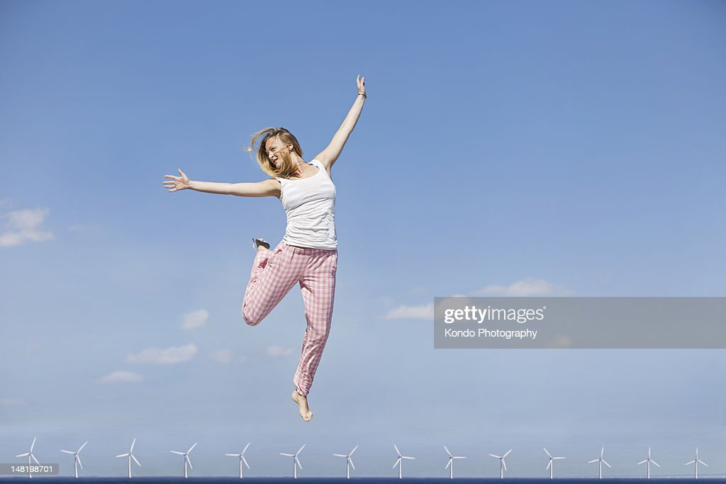 Woman jumping for joy over wind turbines : Stock Photo