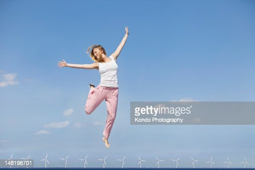 Woman jumping for joy over wind turbines : Photo