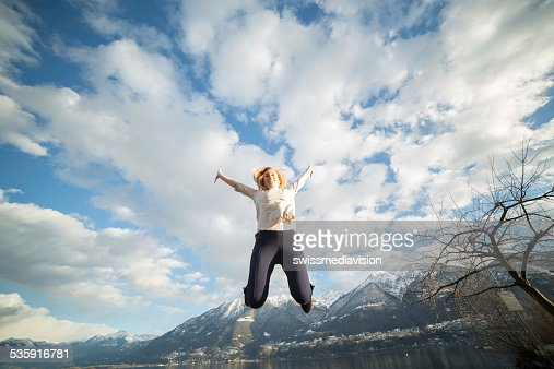Woman jumping high up-Nature : Stock Photo