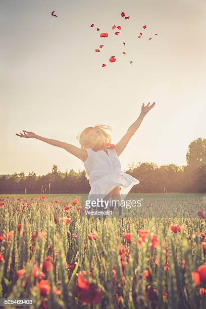 Woman jumping in a poppy field throwing petals in the air