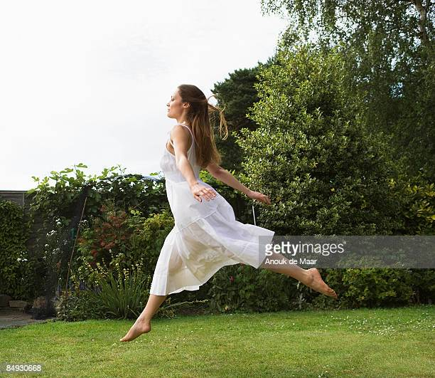 Woman jumping in air in garden