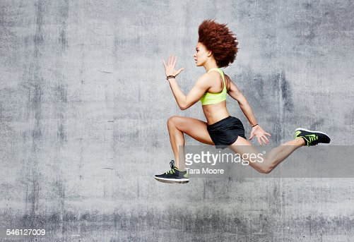 Woman jumping in air in urban studio