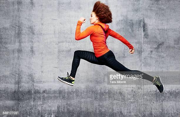 Woman jumping in air in urban studio
