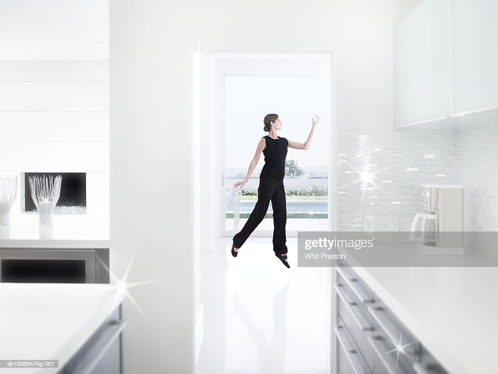 Woman jumping in kitchen : Stock Photo