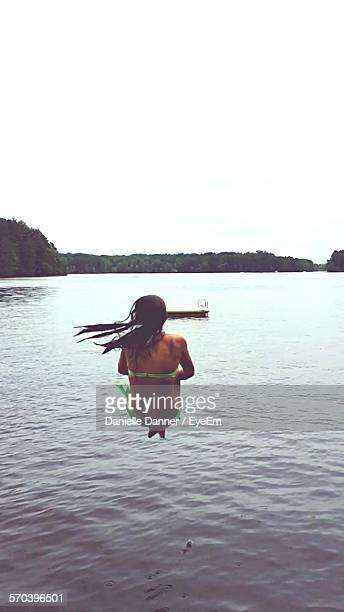 Woman Jumping In Lake Against Clear Sky