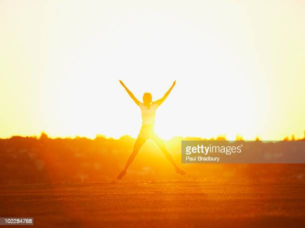 Woman jumping in park at sunset