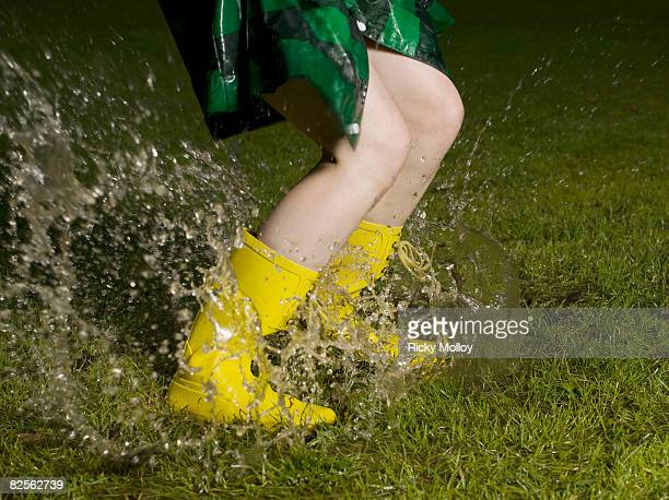 Woman jumping in rain puddle