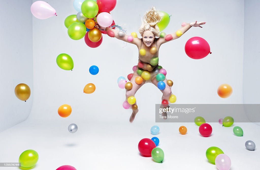 woman jumping in room full of balloons : Stock Photo