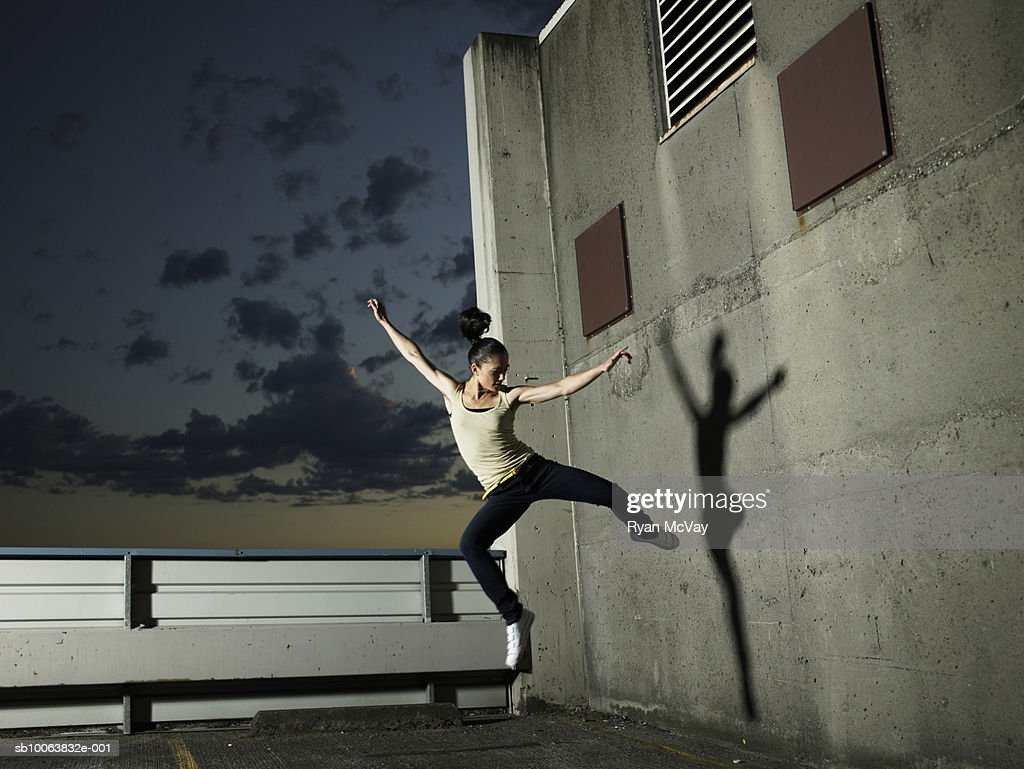 Woman jumping mid air on rooftop carpark : Stock Photo
