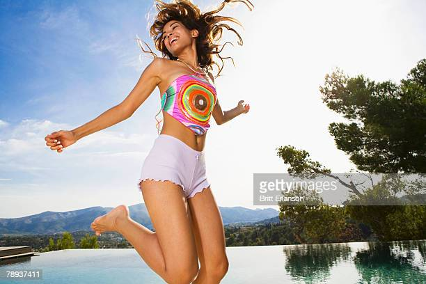 Woman jumping near an infinity pool smiling.