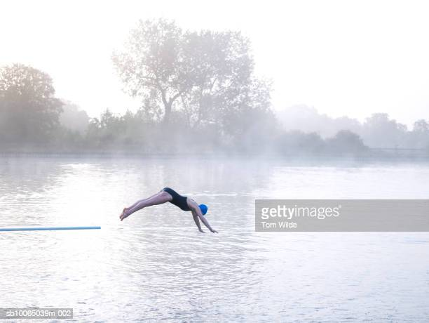 Woman jumping off diving board into lake, side view