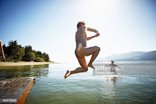 Woman jumping off of floating dock into water
