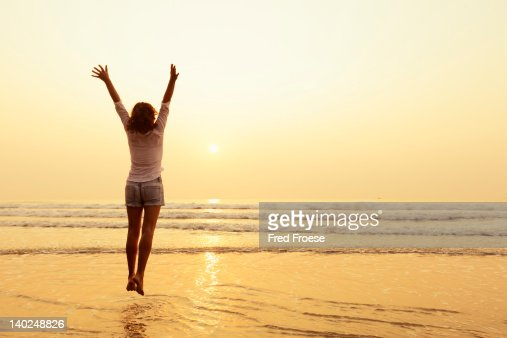 Woman jumping on a beach : Stock Photo