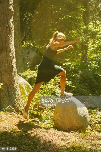 Woman jumping on a stone in the forest