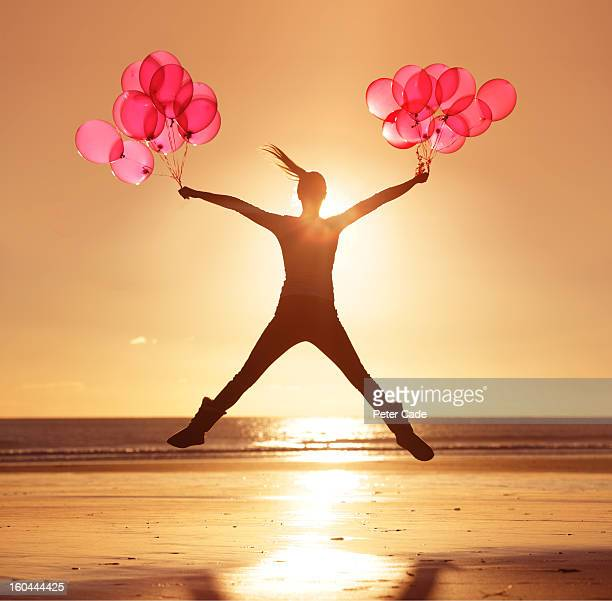 Woman jumping on beach at sunset holding balloons