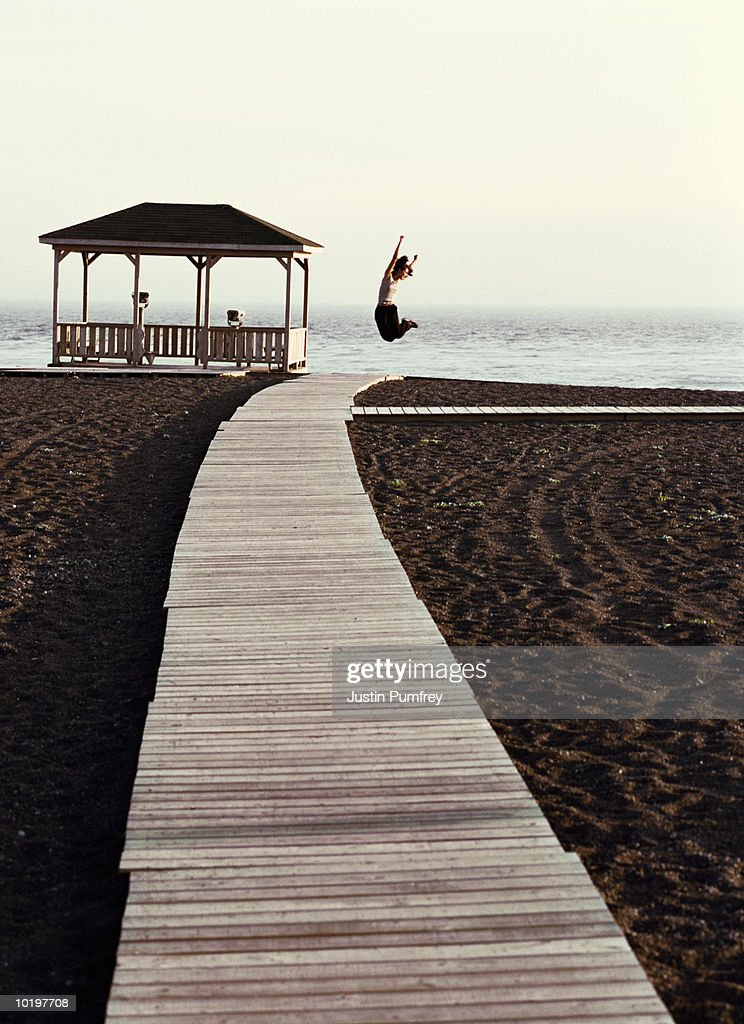 Woman jumping on boardwalk : Stock Photo