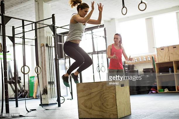 Woman jumping on box with fitness trainer