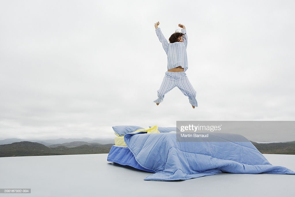 Woman jumping on double bed on platform in rugged landscape : Stock Photo