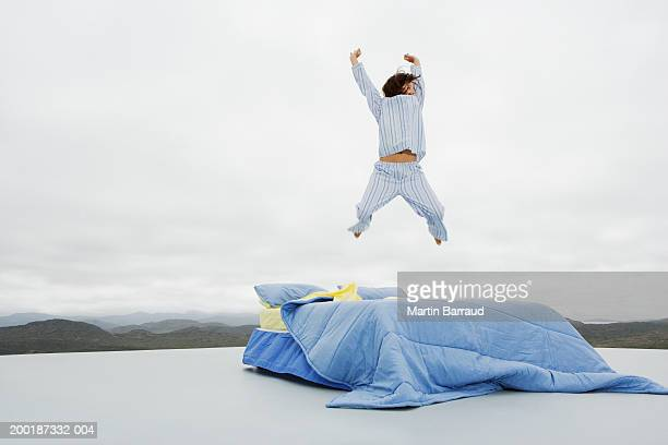 Woman jumping on double bed on platform in rugged landscape