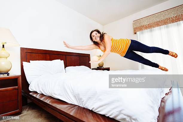 Woman Jumping on Hotel Bed