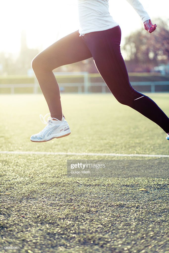 Woman jumping on soccer athletic ground : Stock Photo