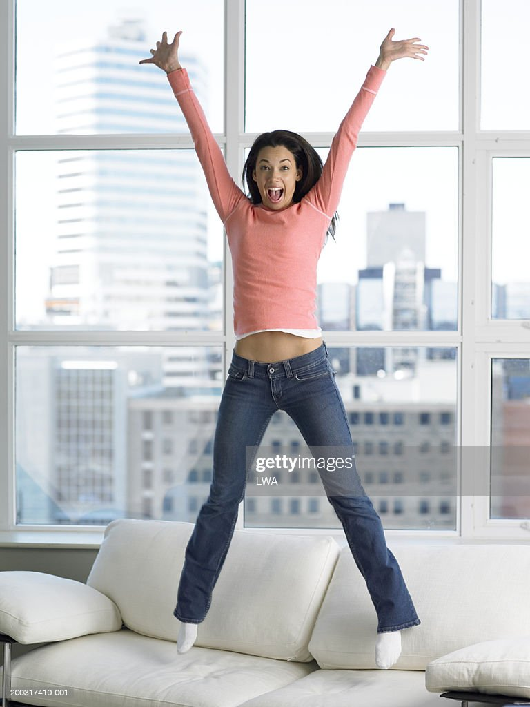 Woman jumping on sofa with arms outstretched smiling, portrait : Stock Photo